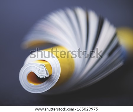 Rolled up magazine against a black background - stock photo
