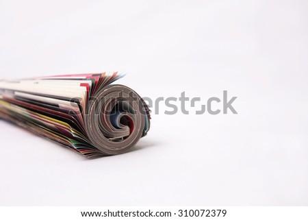 Rolled up magazine isolated on white background - stock photo