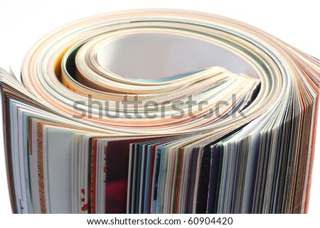 Rolled up magazine on bright background - stock photo