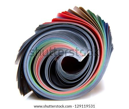 Rolled up magazine on white - stock photo