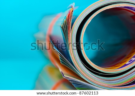 Rolled up magazines on blue background - stock photo