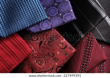 Rolled up modern and classic silk ties on top of each other. Blue, red, purple, bordeaux and black - stock photo
