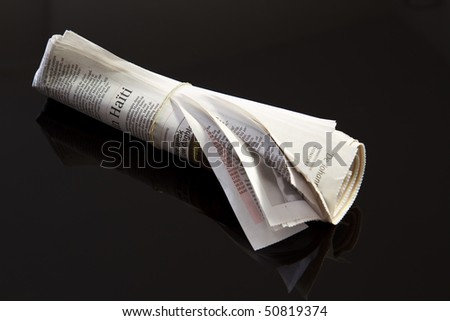 rolled up newspaper with rubber band on black - stock photo