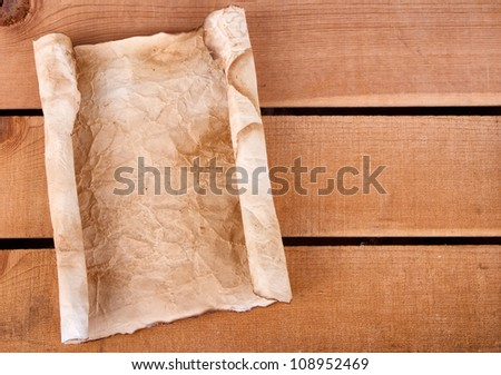 Rolled up old and weathered blank paper on a wooden plank - stock photo