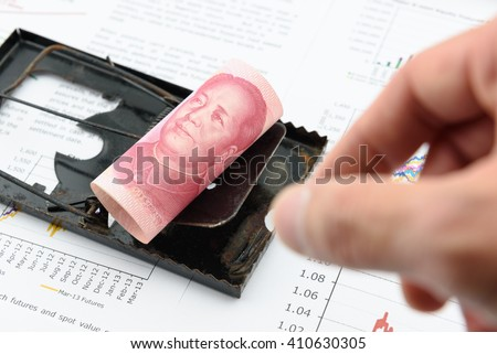 Rolled up scroll of CNY Chinese 100 yuan bill with portrait / image of Mao Zedong on a black rat trap. Using money as a bait to lure someone for illegal / dishonest things. China financial concept. - stock photo