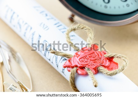 Rolled up scroll of last will and testament fastened with natural brown jute twine hemp rope, sealed with sealing wax and stamped with alphabet letter B. Decorated with an antique clock and glasses. - stock photo