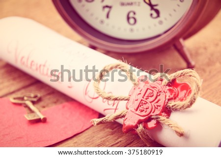 Rolled up scroll of love poem fastened with natural brown jute twine hemp rope, sealed with sealing wax and stamped with alphabet letter B. Decorated with a red mulberry paper heart and vintage clock.