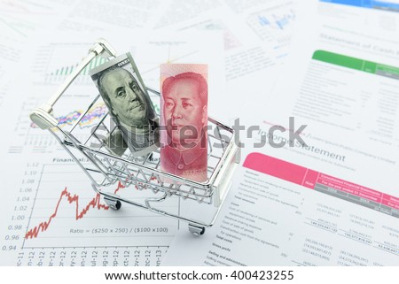 Rolled up scroll of US 100 dollar bill and Chinese Yuan in a trolley with the portrait / image of  Benjamin Franklin and Mao Zedong in the obverse / front side. Placing on a company financial reports. - stock photo