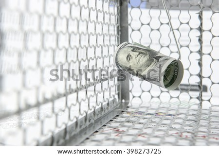 Rolled up scroll of US 100 dollar bill as a lure placed on a hook in a rat trap cage. A concept of using money to deceive naive people for illegal things i.e currency exchange, fake gold trading, etc - stock photo