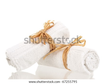 Rolled up towels with reflections on pure white background - stock photo