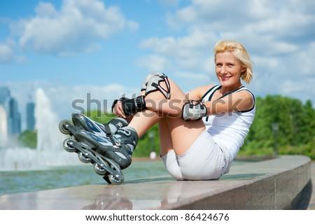 Roller blonde girl resting on the border - stock photo