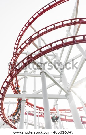 Roller coaster in the amusement park with people in a motion blur