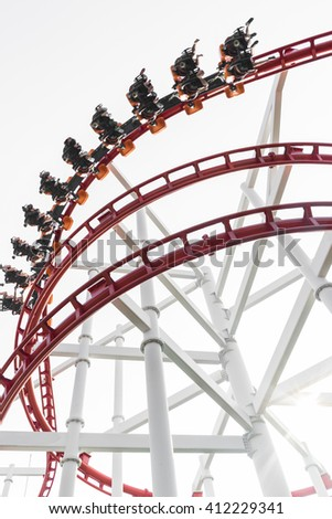 Roller coaster in the amusement park with people in a motion blur - stock photo