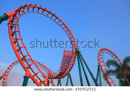 roller coaster loop at sunset. - stock photo