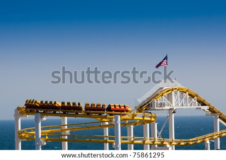 Roller Coaster on Clear Sky and Ocean Background with American Flag - stock photo