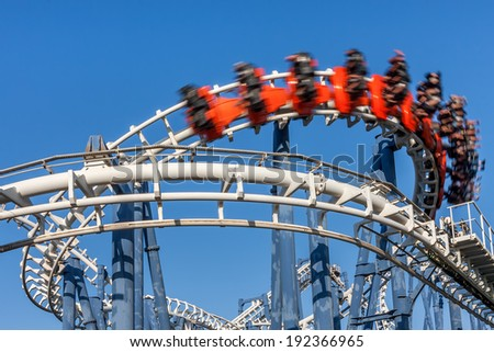 Roller coaster ride under blue sky. - stock photo