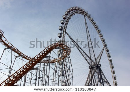 Roller coaster track and ferris wheel - stock photo