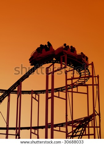 Roller coaster train going down the steep slope - shot against orange sky - stock photo