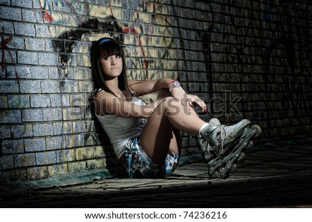 Roller girl sitting against grafitty wall - stock photo