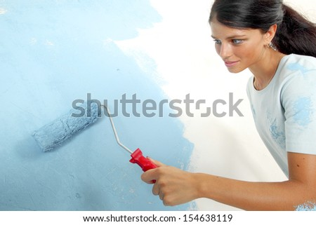 roller in woman hand paint on the wall - stock photo