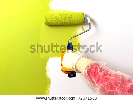 Roller painting wall on green color - stock photo