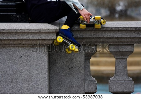 Roller skate girl sitting on a wall