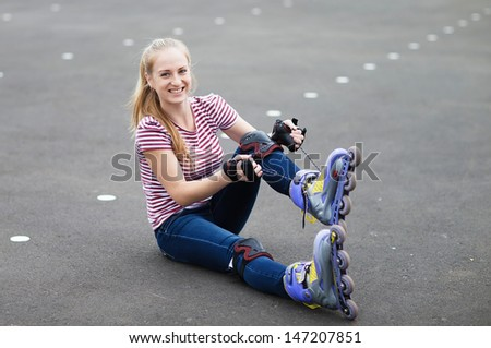 Roller skate girl skating. Young woman putting on skates going rollerblading in urban city park - stock photo