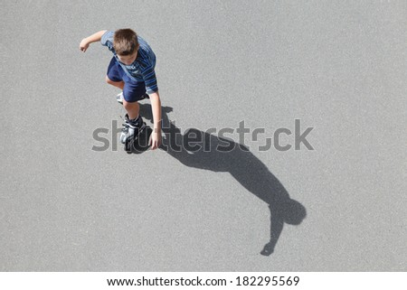 roller skating boy with shadow, top view  - stock photo