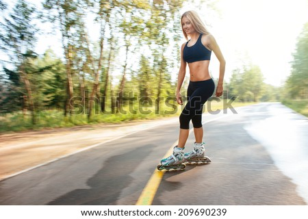 Roller skating sporty girl in otdoor. Caucasian woman in outdoor fitness activities. - stock photo