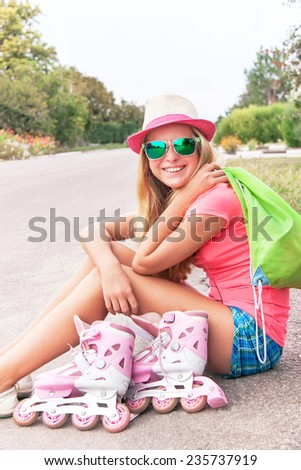 Roller skating teenager (girl) is sitting with roller skating shoes (inline skates), bag, listening music with headphone. Teen wearing sunglasses and having fun. Concepts of youth, sport, lifestyle. - stock photo