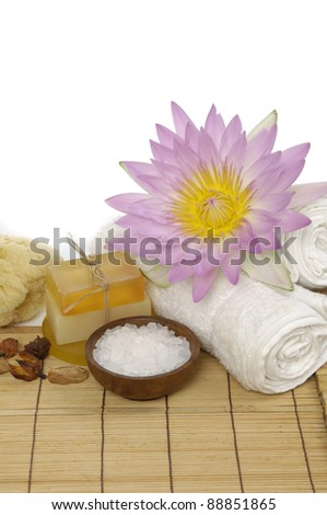Roller towel and soap with a flower and bowl of herbal salt on mat - stock photo