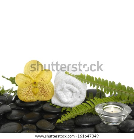 roller towel with green fern and yellow orchid, candle on pebbles - stock photo
