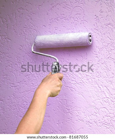Roller with paint on the wall - stock photo