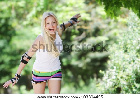 Rollerblade / roller skating woman going skating on inline roller blades. Young happy girl enjoying outdoor workout - stock photo