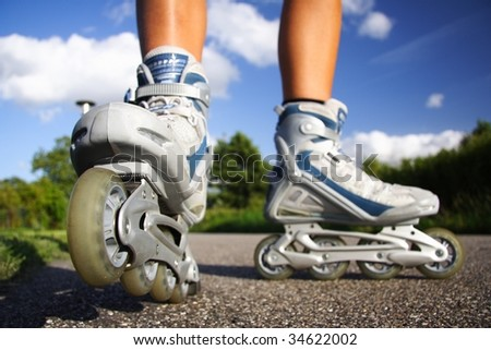 Rollerblades / inline skates closeup in action outdoors on sunny day. - stock photo