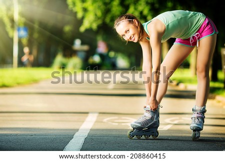 Rollerblading woman. Young attractive female fitness model is having fun skating in a city park in the sunny morning. Sports lifestyle concept.  - stock photo