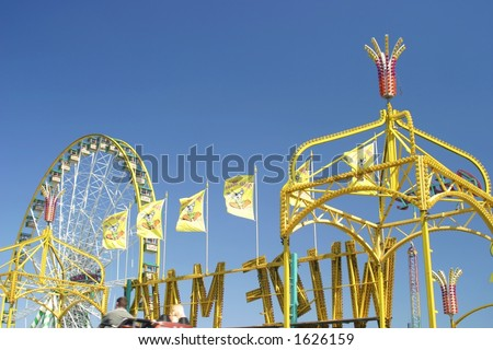 rollercoaster on a carnival area with a big wheel in the background