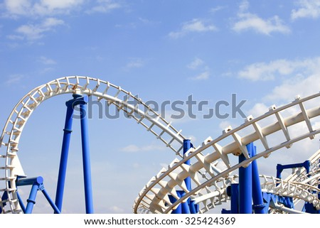 Rollercoaster tracks with blue sky in the background - stock photo