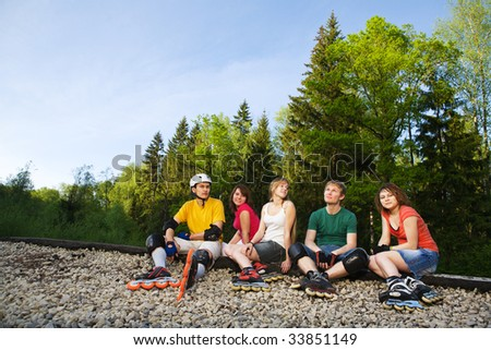 Rollers talking and sitting at park - stock photo