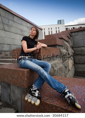 Rollerskating girl in blue jeans sitting on granite plate - wide angle portrait