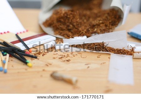 Rolling a cigarette, tobacco bag, rolling paper, filters and matches on a table, unhealthy life style. Focus on tobacco in rolling paper - stock photo
