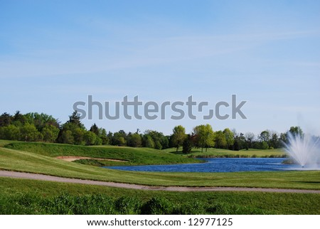rolling fairway with flag and fountain on golf course
