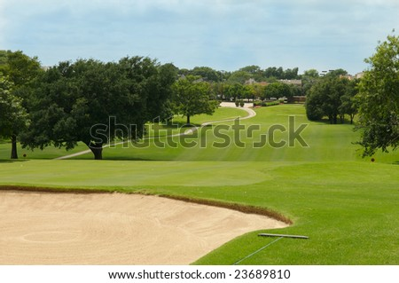 rolling golf fairway with blue sky, trees, and sand bunker