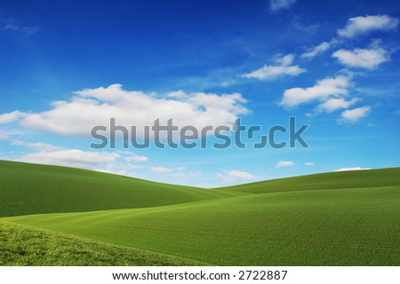 Rolling green hills and a blue sky - stock photo