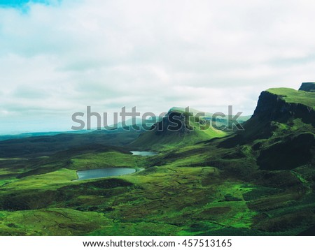Rolling green hills and lakes on the Isle of Skye in Scotland. - stock photo