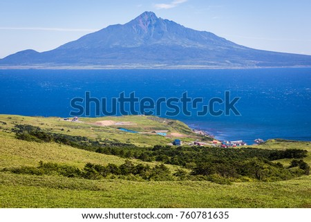 Rolling hills of sasa bamboo grass and wildflowers cover the southern tip of Rebun Island, Japan; village of Shiretokomanai and Mt. Rishiri are in the distance