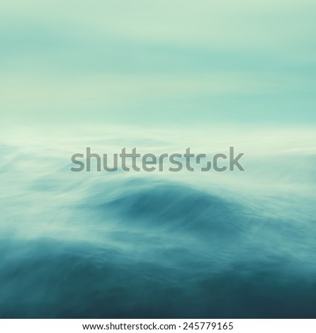 Rolling ocean waves in stormy conditions.  Seascape made with blurred panning motion and cross-processed colors. - stock photo
