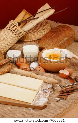 Rolling pin and dough for baking with scattered flour and a bowl of flour with eggs. - stock photo