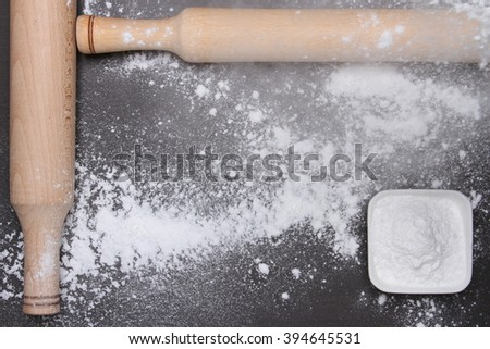 Rolling pin and flour on table. Top view.