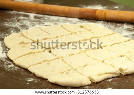 Rolling pin and the cut dough for preparing dumplings. - stock photo